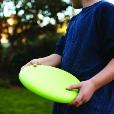 Boy playing with green frisbee