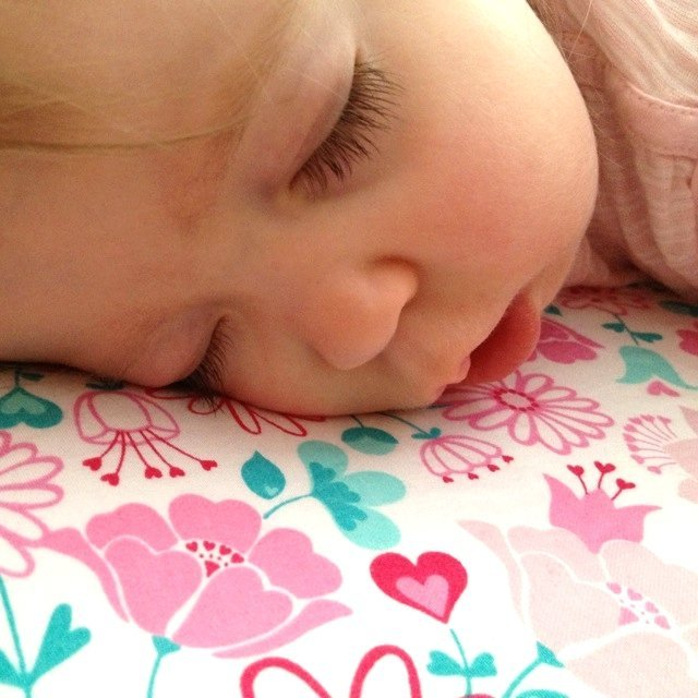 Baby laying on floral cot sheet