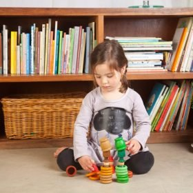 child stacking loose parts